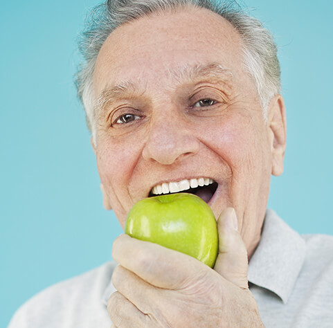 senior man eating a green apple