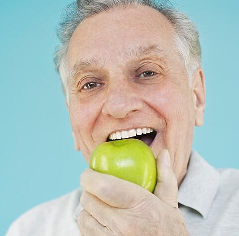 senior man eating a green apple