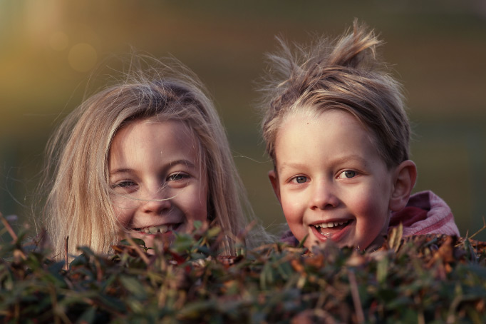 Two smiling blonde siblings, a girl and boy, have disheveled and windblown hair while peeking over a hedge