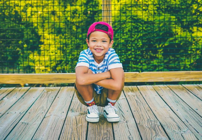 Young boy in a backwards red baseball cap and blue striped shirt crouches on a wooden bridge while smiling