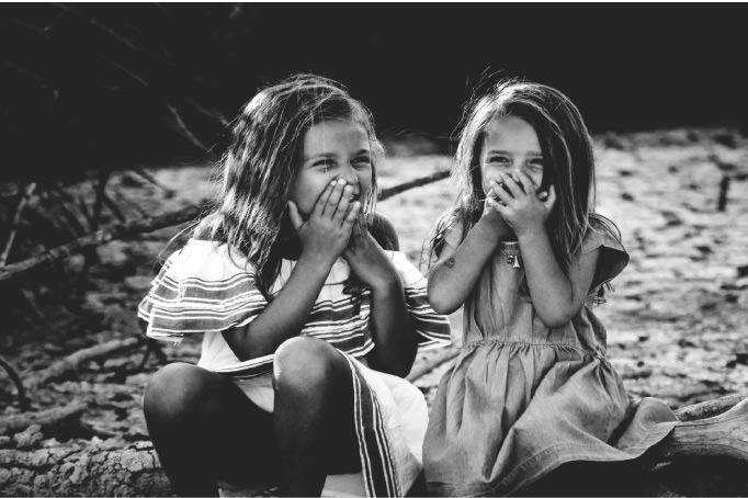 two young girls sitting holding their mouths shut with bad breath