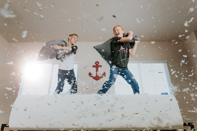 A young brother and sister smile and laugh as they have a pillow fight on a bed with feathers all around them in the air