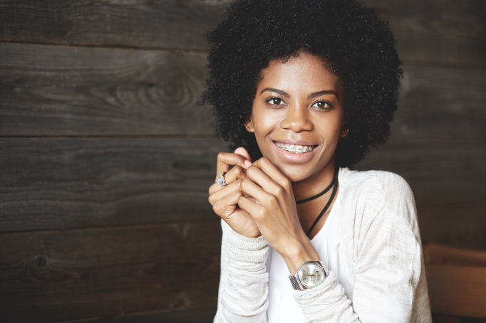 Curly-haired woman with adult braces smiles while wearing a white shirt