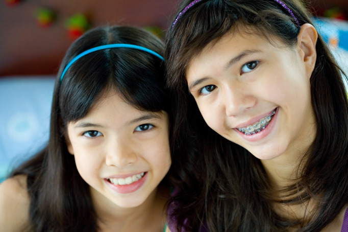 2 dark-haired smiling girls, one wearing braces