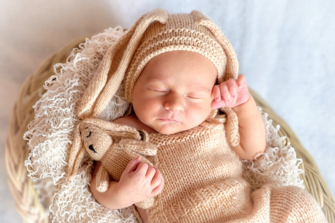Aerial view of a sleeping baby wearing a crocheted sweater and rabbit ears beanie in a basket while holding a bunny