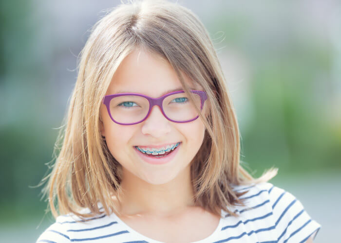 Blonde girl with braces and purple glasses smiles outside