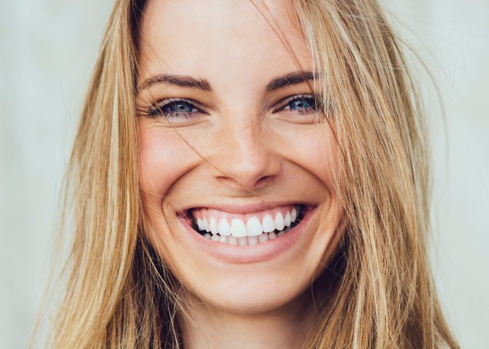 Blonde woman smiles because she is relaxed about her stress-free dental visit thanks to dental sedation