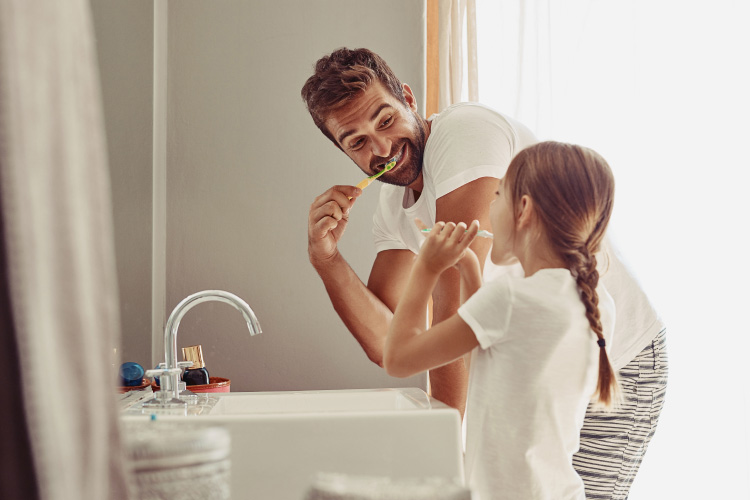 Dad & young daughter brushing their teeth together in front of the bathroom sink