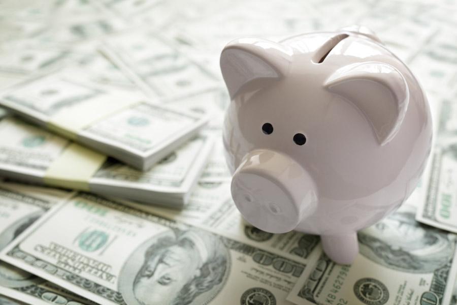 piggybank sitting on a pile of hundred dollar bills