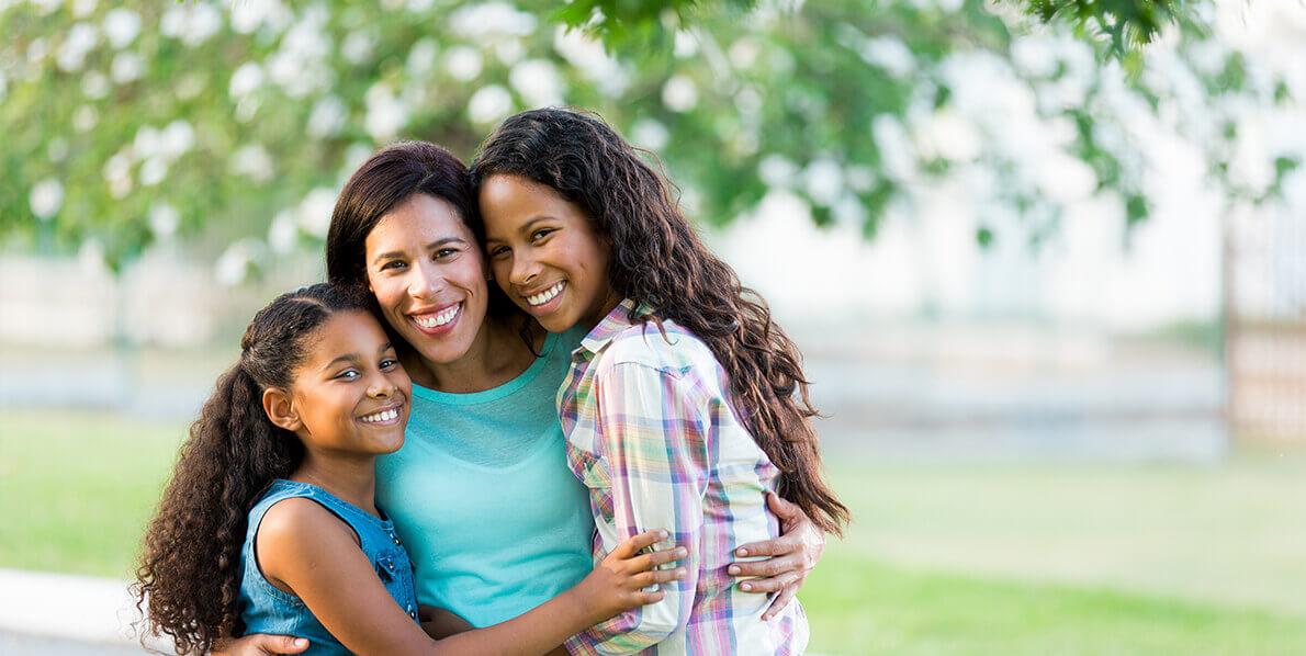 smiling mother being hugged by her two daughters