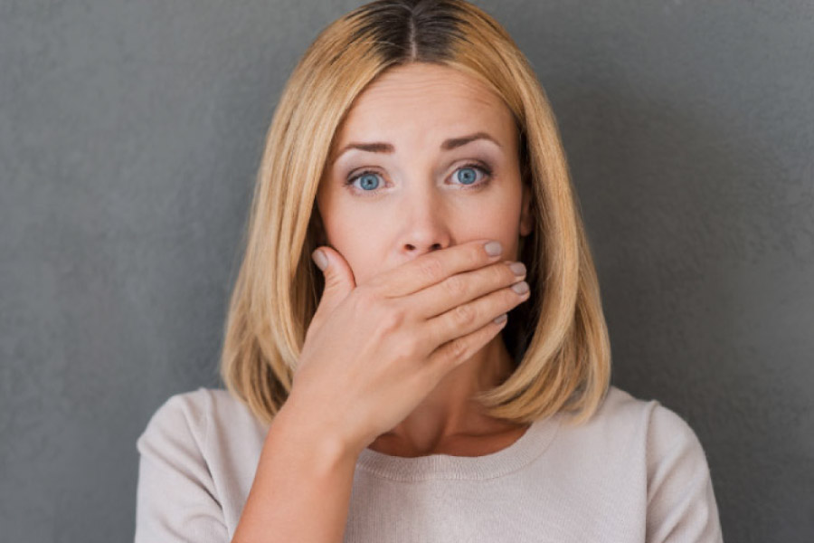 woman covers her mouth with her hand to hide gum disease