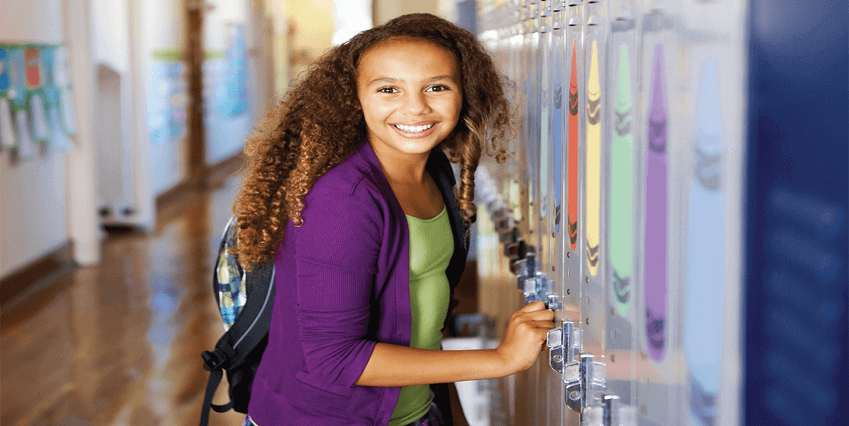 Teen girl posing in front of a school locker